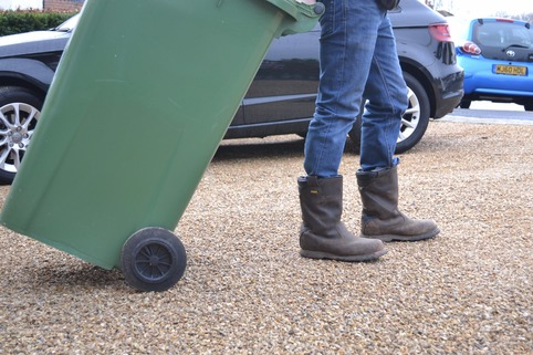 Wheelie bin being rolled across stabilised gravel driveway